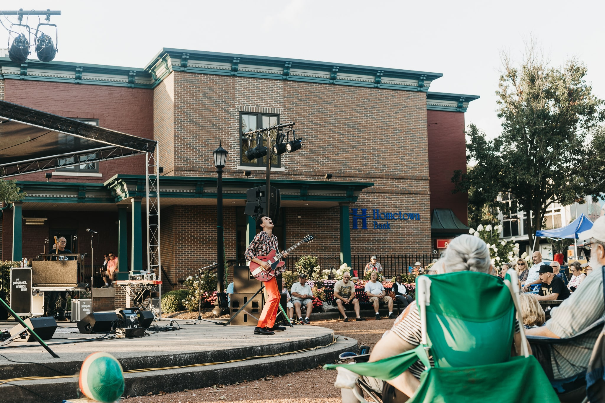 guitarist playing in front of crowd of people at hometown bank concert